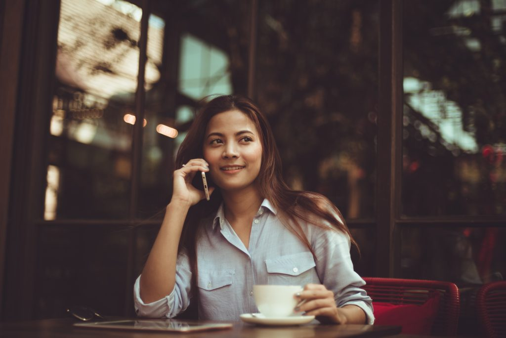 woman on cell phone with coffee